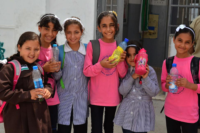 Palestinian children bringing water to school